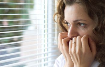 A scared woman biting her nails looking through the window.