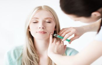 Young woman receiving facial injection treatment.