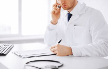 A doctor talking on the phone and taking notes.