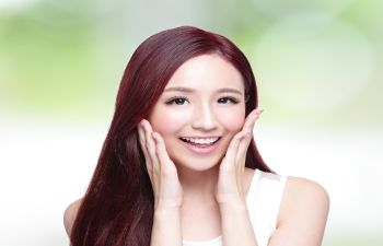 Smiling young woman touching her cheeks with open hands.