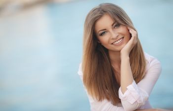 Smiling young woman leaning her chin on her hand.
