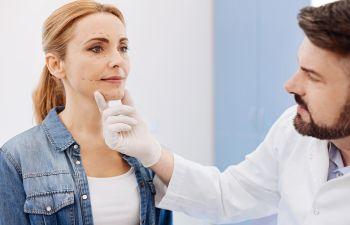 A doctor examining woman's face.