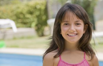A young smiling girl with asymmetrical facial appearance.