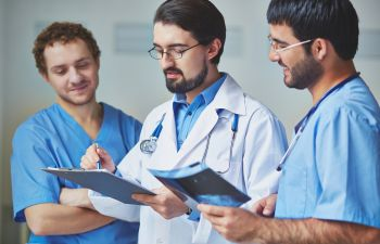 Group of physicians discussing medical records.