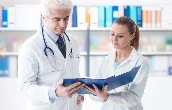 Two doctors reading medical records